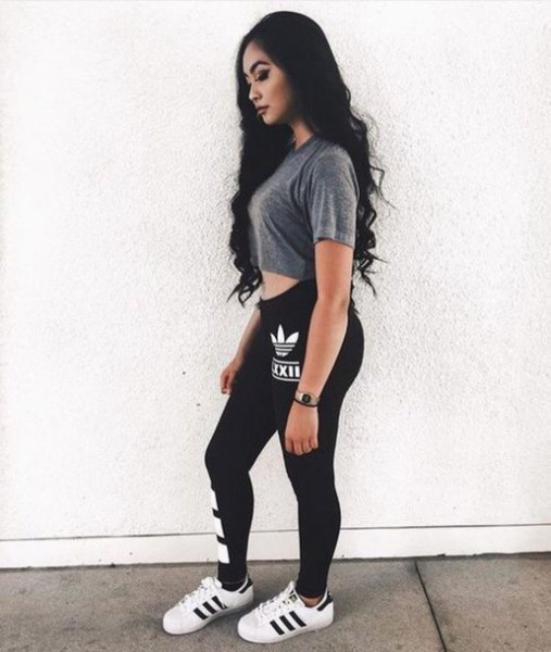 gray short t-shirt with black adidas leggings and white sneakers