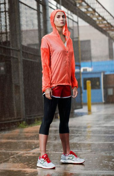 red windbreaker with black, short leggings and gray sneakers
