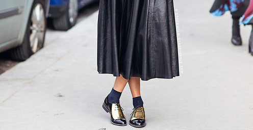 Black leather midi pleated dress with crew socks and gold wintip oxfords