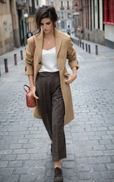 Camel longline wool coat with white silk top and gray trousers with wide legs