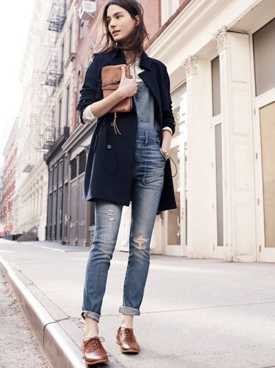 black long wool coat with gray-blue jeans with cuffs and brown shoes