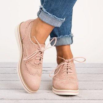 Light pink Oxford evening shoes with blue slim-fit jeans with cuffs