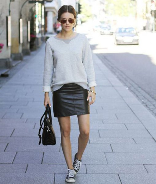 gray sweatshirt with mini skirt and black leather sneakers