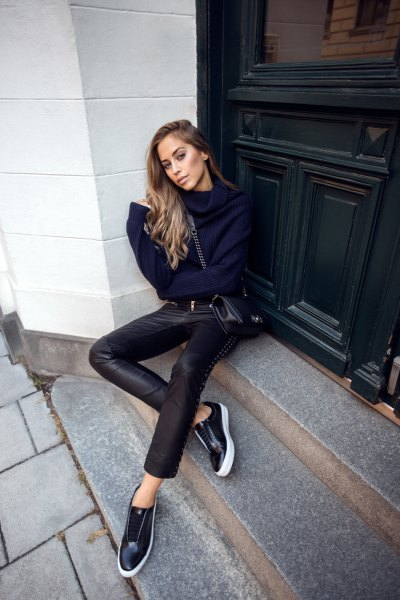 Navy blue knit sweater with a cowl neck and low black leather sneakers