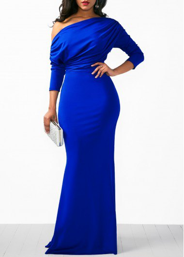 A strapless royal blue long sleeve dress with a white clutch wallet