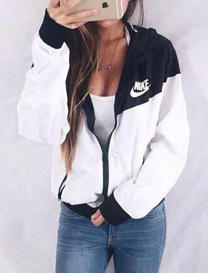 white and black Nike windbreaker with low tank top and jeans