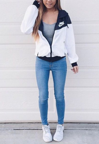white windbreaker with a gray, form-fitting tank top and blue skinny jeans
