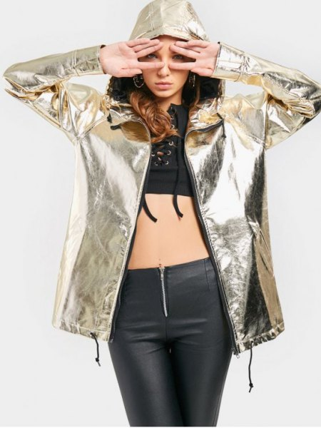 silver metallic windbreaker with black crop top and leather gaiters