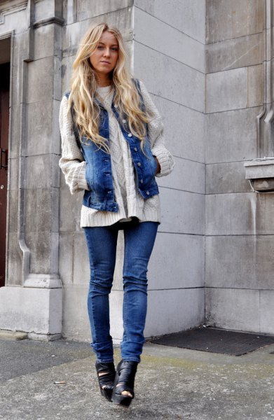 white cable knit sweater with blue jeans motorcycle vest and boots