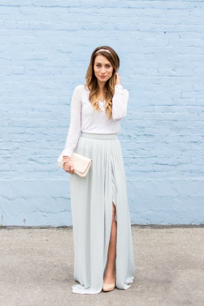 Long sleeve floor-length dress with gathered waist and white clutch