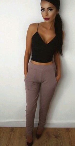 black, short vest top with a deep V-neck and gray, high-waisted suit pants
