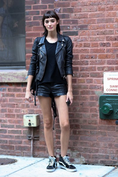 black leatherette jacket with mini denim shorts and canvas sneakers