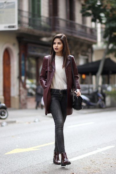 long maroon leather jacket with white sweater and gray jeans