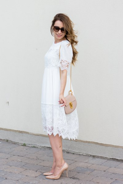 white babydoll midi dress with scalloped hem and light pink shoulder bag
