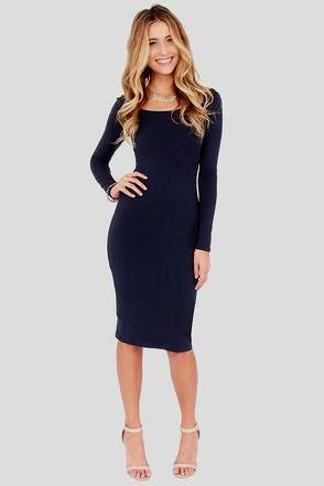 Navy blue long sleeve midi dress with a boat neckline and white heels with open toes