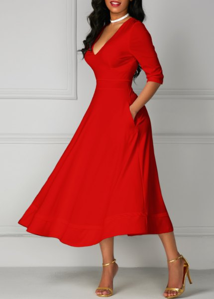 red half-arm with a V-neck and flared midi dress with gold heels