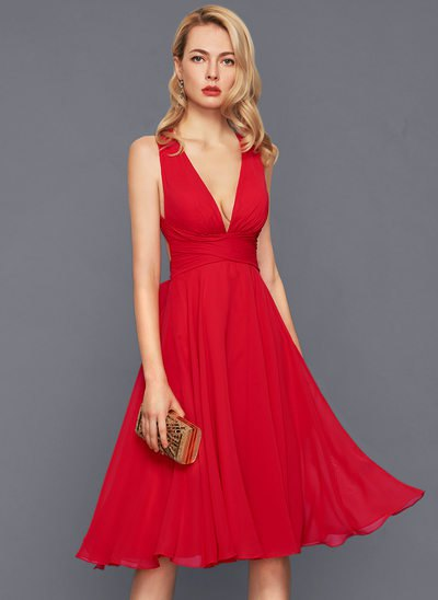 red midi dress with deep v-neck and flared midi dress with clutch wallet