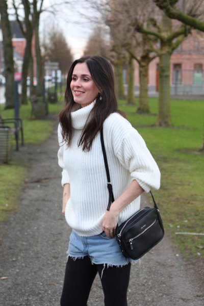 white, thickly ribbed turtleneck sweater with blue denim shorts and leggings