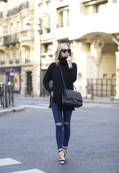 black turtleneck side slit sweater with dark blue skinny jeans with a torn knee