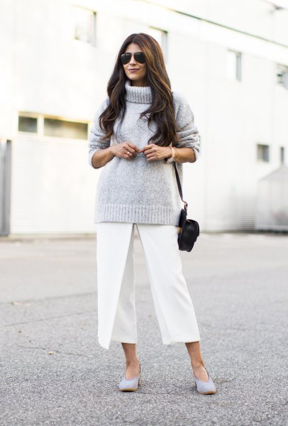 gray knitted sweater with turtleneck and white, short-cut trousers with wide legs