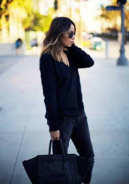 black, roughly knitted sweater with V-neck and dark, slim fit jeans