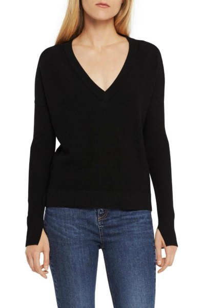 black knit sweater with low V-neck and dark blue skinny jeans