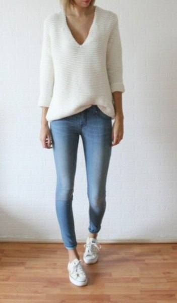 white knitted sweater with a relaxed fit and V-neck and light blue skinny jeans