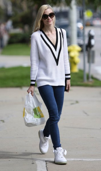 white and black rib sweater with V-neck and dark blue skinny jeans