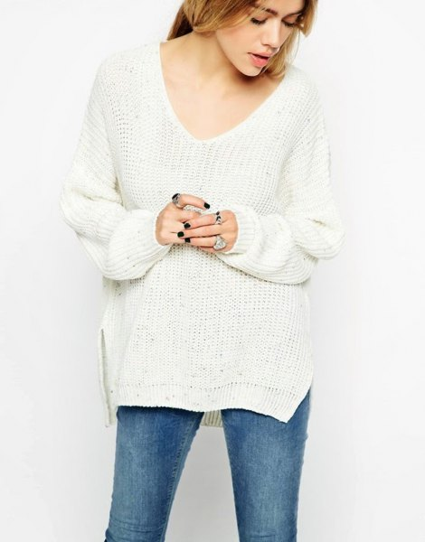 Side slit white sweater with blue skinny jeans