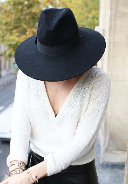 black felt hat with white v-neck sweater and skinny jeans