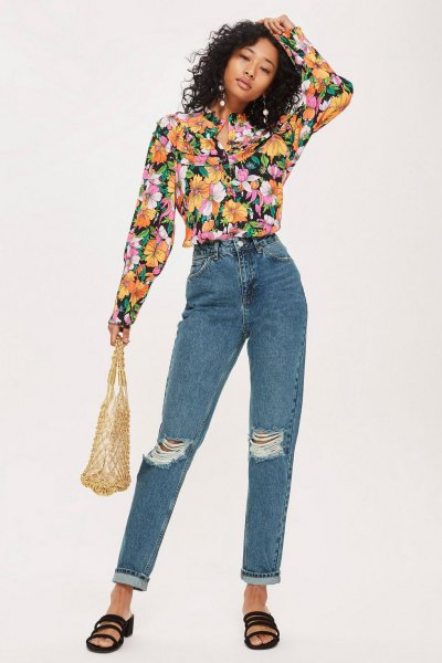 black blouse with floral pattern and blue torn jeans