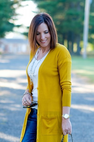 mustard-colored knit sweater with white t-shirt with a scoop neck and blue jeans