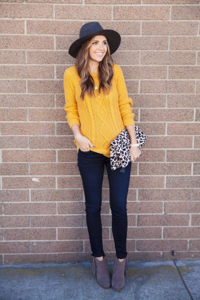 Cable knit sweater with black felt hat and thin dark jeans