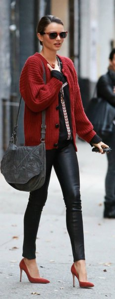 red ribbed cardigan with black top and leather gaiters