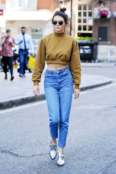 green, short-cut sweatshirt with mock-neck and blue, high-waisted mom jeans
