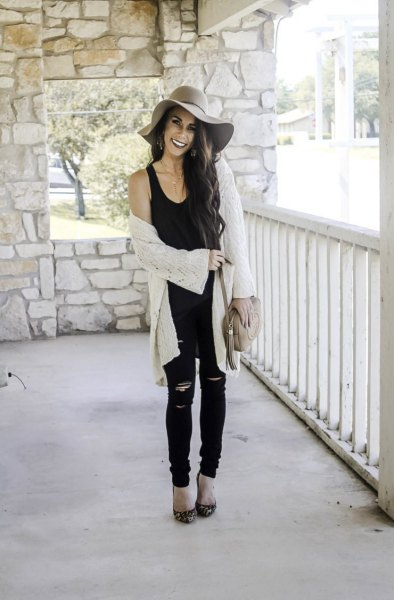 black tank top with a scoop neckline, white cardigan and floppy hat
