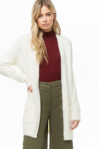 white, flaky long cardigan with green, ribbed sweater with mock-neck and trousers with wide legs