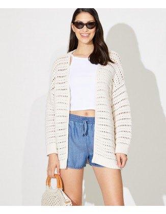 white oversized crochet jacket with shortened t-shirt and blue elastic waist shorts