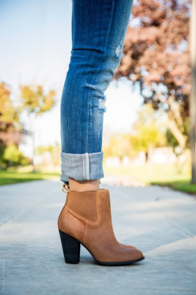 blue jeans with cuff and brown leather boots with ankle heel