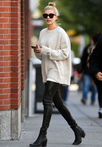 cream-colored oversized knit sweater with black leather gaiters