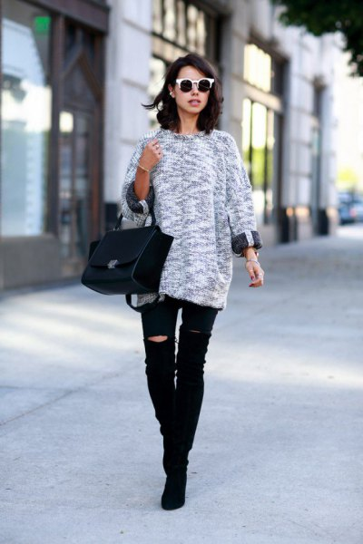 gray mottled knit sweater with black, torn knee jeans