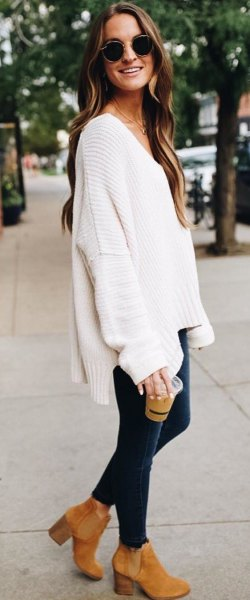 white, chunky V-neck sweater with dark blue skinny jeans and camel boots