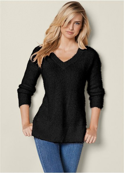 black slim fit knit sweater with V-neck and blue skinny jeans
