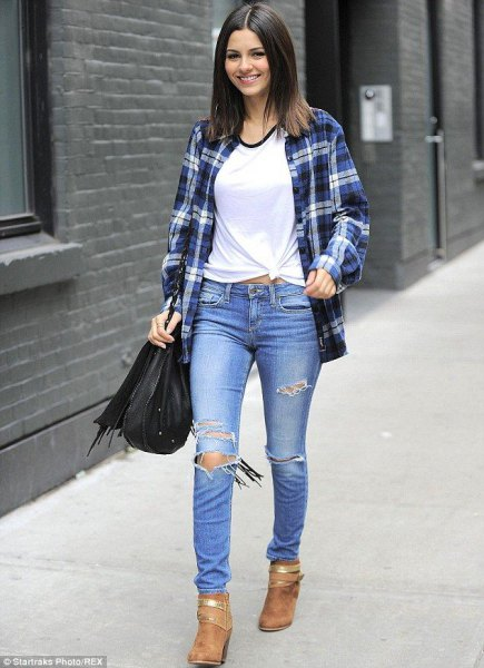 Flannel shirt with a white knotted t-shirt and torn jeans