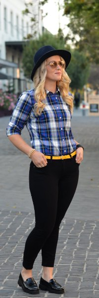 blue and white shirt with yellow belt and black skinny jeans