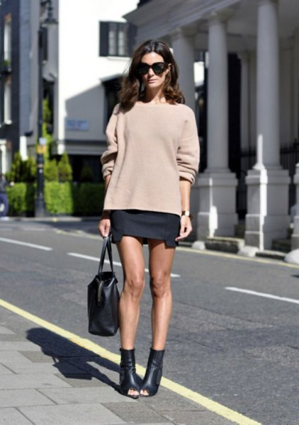 blush pink chunky sweater with black mini skirt and open leather ankle boots