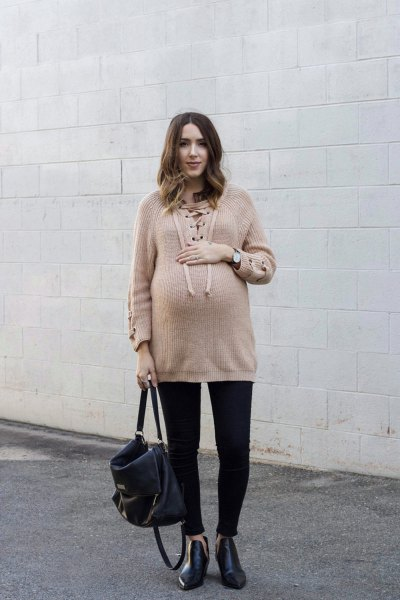 Light brown oversized sweater with black jeans with cuffs and leather boots