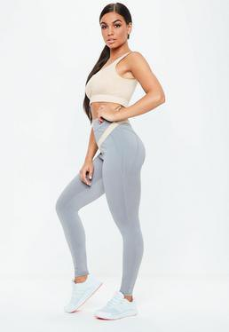 Light pink crop top with gray, high waisted, seamless leggings and white sneakers