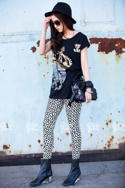 black graphic t-shirt with high-heeled leather boots and felt hat