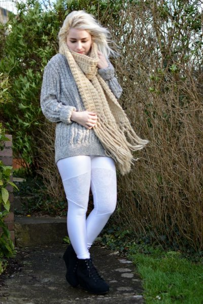 gray, coarse-grained knit sweater with a blushing fringed scarf